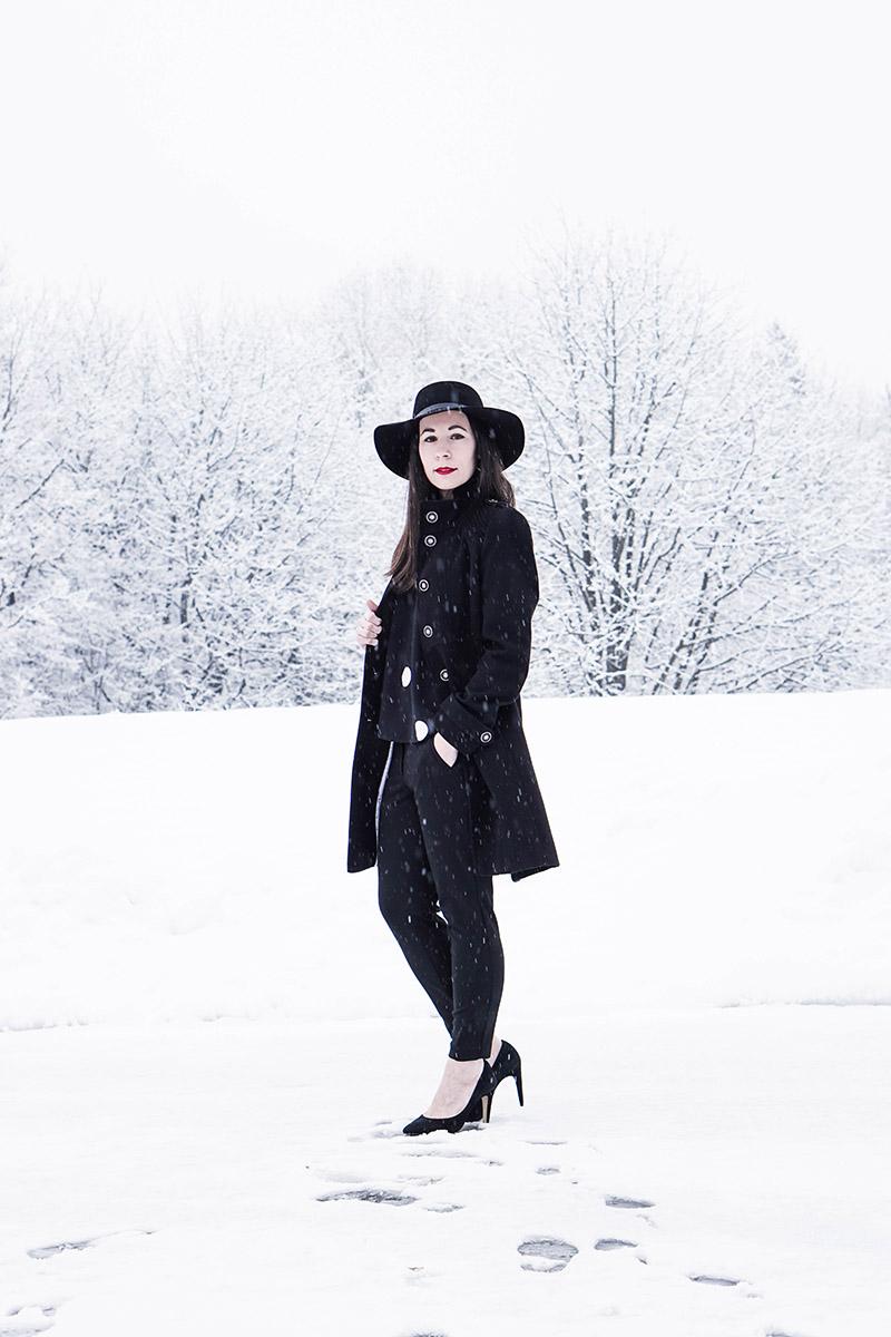 Heute trage ich ein klassisches Outfit mit Hut. Die dominierende Farbe ist schwarz, die einzigen auffälligen Accessoires sind meine Statement Ohrringe aus Silber.